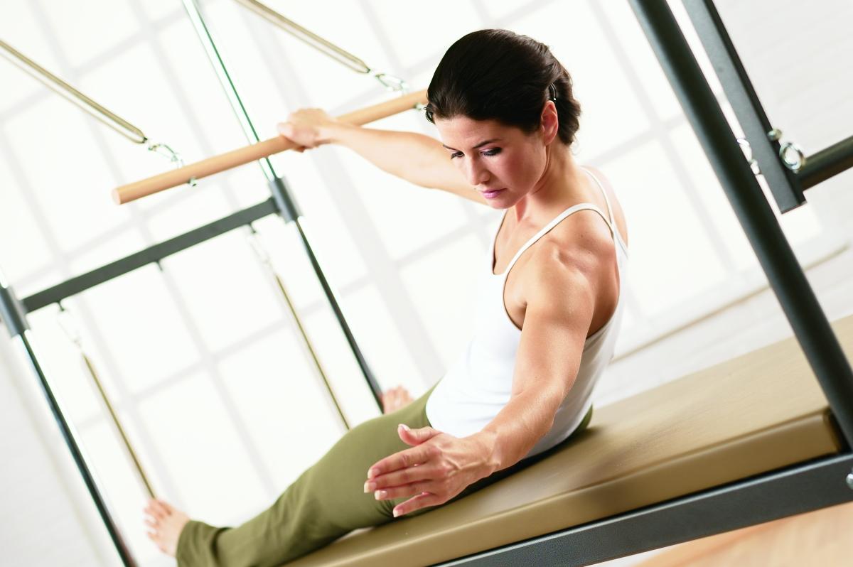 a woman performing Port de Bra on Pilates Cadillac