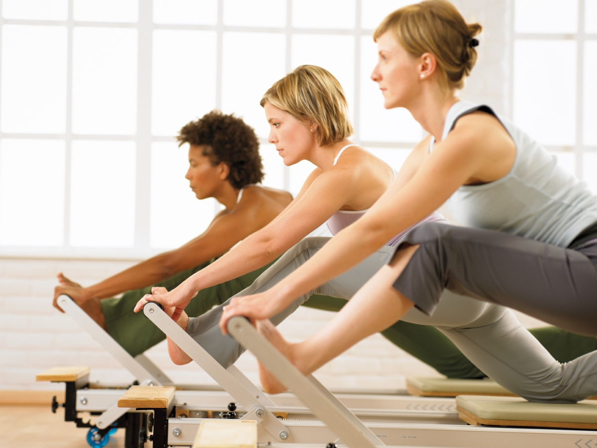 a group performing a Pilates exercise on Reformer