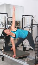 student demonstrating Yoga pose on Pilates Reformer