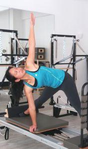 student demonstrating Yoga pose on Pilates Reformer