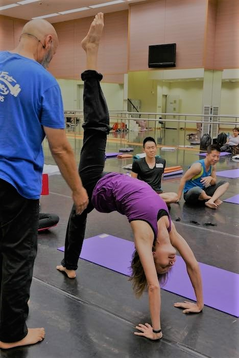 stretch student doing a standing back bend llifitng one leg in the air