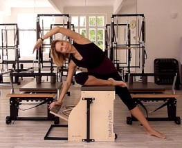 Pilates instructor demonstrating mermaid exdercises on Stability Chair
